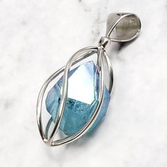 Add this beautiful Aqua Aura Quartz Pendant to your crystal jewelry collection! Features a sterling silver spiral twist cage that holds an Aqua Aura Quartz crystal point with a time link portal face! This type of quartz is a must have for past life regressions and future time line meditations.  The Aqua Aura Quartz crystal point in this pendant radiates soothing water blue tones. Infused with gold, this precious metal is known for bringing prosperity and vitality. Aqua Aura Quartz, Quartz Crystal, Water Blue, Crystal Fashion, Blue Tones, Crystal Jewelry, Precious Metals, Cage, Portal