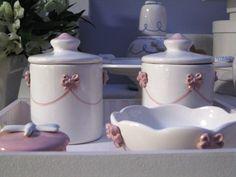 Kit de Higiene de bebê ; 9,5D x 14A <br>2 potes com tampa de cerâmica pintada à mão 9,5D x 14A <br>1 bowl para água de cerâmica pintada à mão 13Dx5,5A <br>1 bandeja de madeira pintada 35x 35 <br>OBS. A caixinha rosa da foto é só ilustrativa, vendida à parte, não faz parte do KIT <br>Todas as peças são produzidas no atelier e podemos fazer em outras cores. Consulte-nos.