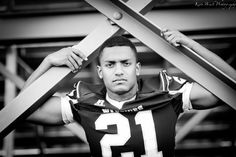 Kari Bruck Photography high school senior session pose idea for football players. High school senior boy inspiration for posing for football. Senior Pictures for a guy in a black and white image.Sports or Sport pictures. by sonja