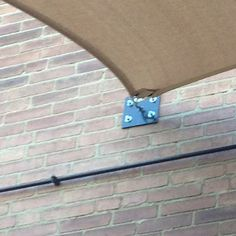 Inexpensive way to add an awning outdoor fabric was attached to building wall bracket and then with post outside edge of patio