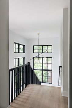 Modern Farmhouse Stairway The combination of black railings, black windows, a modern black and brass chandelier with white shiplap really brings this entire space to the next level. Impressive, dramatic yet neutral #modernfarmhouse #stairway #staircase