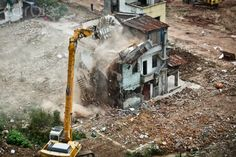 An excavator tears down a building at Yangji village in Guangzhou city, south Chinas Guangdong province, 21 March 2012. The second-phase demolition of Yangji village Wednesday (21 March 2012) began in Guangzhou city, south Chinas Guangdong province. It is said that 4 buildings which cover an area of 326.21 square meters will be demolished this time. Policemen and workers were busy at the scene. A woman who lived there tried to protect her house being destroyed.