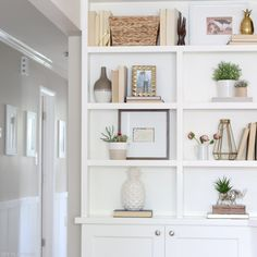 Neutral bookshelves with greenery and personality. Love these white built-ins and all of the pretty accessories on them.