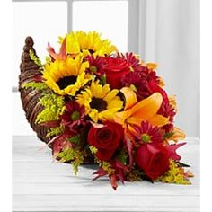 @Stacy Stone Stone Delfelder Flowers proudly presents the Better Homes and Gardens® Fall Harvest™ Cornucopia. Capture the essence of the autumn season with this inspiring and colorful arrangement. Rich red roses, bright and brilliant sunflowers, orange Asiatic lilies, burgundy daisies, solidago, red glycerized oak leaves and lush greens are beautifully arranged in a natural cornucopia basket that speaks of harvest traditions with each gorgeous bloom.This is a 3 sided arrangement.
