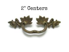Vintage French Provincial drawer pull and both screws -Measurements: Just over 5 wide, 1.5 tall, with 2 centers (from the middle of one screw hole to the middle of the other) -Original aged brass patina -Only one available, but see more 2 center pulls here: https://www.etsy.com/shop/Fairyhome?ref=hdr_shop_menu&search_query=a2cc   See more ornate and French Provincial drawer pulls here: https://www.etsy.com/shop/Fairyhome?section_id=81...