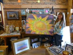 """Peg Anderson of J. P. Frameshop and Western Edge Gallery with Cris Fulton's """"Sunverve"""" drawing. August, 2015, Located at 6 W. Villard in Dickinson, North Dakota."""