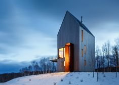 Plates of weathering steel frame the tall doorway to this timber-clad home, designed by architects Design Base 8 and Omar Gandhi for a remote site on Canada's Cape Breton.