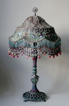 Antique metal lamp base holds a colorful Balinese shade in colors of pink, aqua and blue. Shade is covered in vintage silver Indian sari appliqués and era netting and floral trim. Colorful hand beaded fringe adorns the bottom of the shade. Victorian Lamps, Antique Lamps, Antique Lighting, Antique Metal, Chandeliers, Chandelier Lamps, Glass Lamps, Art Nouveau, Art Deco