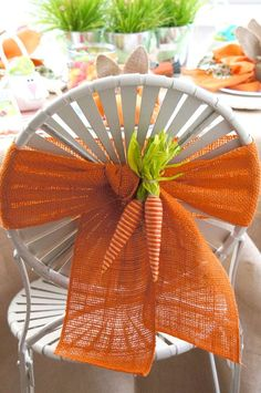 Orange burlap and carrots wrap a chair for a sweet Easter theme.