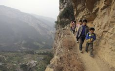 Xu Liangfan escorts school children along a cliff path as they make their way to Banpo Primary School in Shengji county in Guizhou province. Located halfway up a mountain, the school has 68 students of which about 20 live in the nearby Gengguan village. Students from Gengguan have to edge their way along the narrow cliff path to go to class everyday, alongside Xu who would escort them. The path, which was carved from cliffs over 40 years ago, is the only route between Gengguan village and…