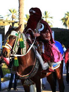 """TRIPOLI, LIBYA - MARCH 13: A Libyan woman wearing traditional clothes rides a horse during an event to mark the """"National Day of Traditional Dress"""" at es-Suheda Square in Tripoli, Libya on March 13, 2017. ( Hazem Turkia - Anadolu Agency )"""
