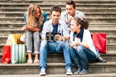 Four friends using a tablet sitting on staircase Royalty Free Stock Photo