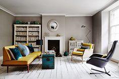 żółta kanapa z fotelem,turkusowe poduszki,turkusowy kufer w roli stolika,biala francuska biblioteczka