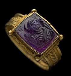 Gold filigree and beaded ring, the broad hoop supporting the square bezel set with an amethyst cameo bust of the Virgin Mary, veiled, hands raised in prayer, inscribed in Greek letters MR OY. (Mary Mother of God), facing front. The back is incised with a cross and the Greek letters IC XC (Jesus Christ) to each side of the upright. C. 1100.