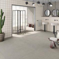Klassiskt 15x15 kakel med ett betongliknande golv kan lyfta arkitekturen och möblerna i rummet. Här får de olika svarta detaljerna ta plats.