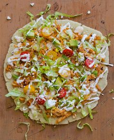 Arepa Pizza - arepa crust topped with sweet chipotle chicken, cilantro yogurt sauce, and other arepa toppings.