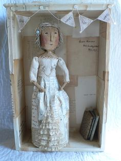 gentlework -She lives in a drawer covered with the title pages from vintage books. Her paper and lace skirt is made from words and she also wears them in her hair. She has a little stock of vintage books with her as she never likes to be without some reading matter...
