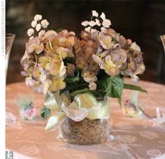 For the reception, the mother of the bride created centerpieces using silk flowers in the wedding day colors. All the different blooms, including gardenias, hydrangeas, daisies, and hyacinths, sat atop the tables.