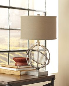 Lambert Table Lamp - This armillary lamp features a marbled finish over its steel construction. It is complemented by a deep khaki-colored hardback drum shade.