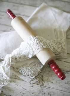 Vintage red handled rolling pin and white lace