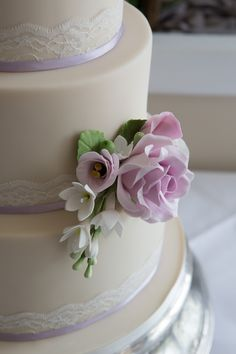 Simple yet elegant wedding cake, lace and lilac ribbon detailing. With hand crafted sugar rose and flower detailing.