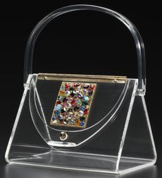 Lucite Lux purse, 1950s. Ladies changed the color of the purse by changing which scarves they had inside it to hide the contents of the bag.