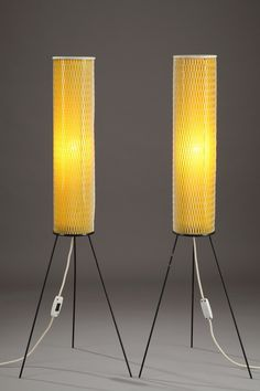 Lampstand of the 50's withtubular yellow plastic structure resting on three black metal feet.