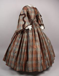 1850s: This plaid silk dress is part of the collection of the American Textile History Museum in Lowell, Massachusetts. Interesting how it's devoid of any ornamentation except on the sleeves.