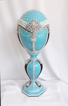 "Breakfast At Tiffany's musical egg that plays Moon River. The outside is the famous Tiffany blue and has the pearl/rhinestone brooch choker she wore, the black velvet stripes represent the ""little black dress"" she wore."