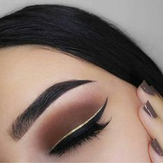 Bold brows with a deep chocolate brown eyeshadow topped with black winged liner and gold streak nestled above.