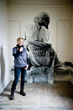 The artist YZ stands in front of the woman who has emerged from the wall, as street artists take over bath-house | MuseumZero