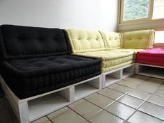"A ""sectional sofa"" made of wood shipping pallets and wonderful cushions. - Sala decorada com os Paletes Oasis by Madeira Usada, via Flickr"