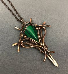 A copper wire wrapped pendant with a Malachite gemstone . The pendant has been tarnished to antique it and then polished to reveal the weaves highlights. The pendant hangs from an oval soldered link chain which closes with a lobster clasp. The length can easily be adjusted by closing