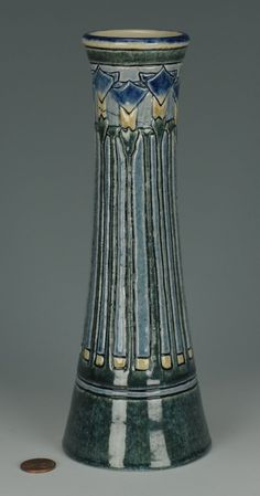 A Newcomb art pottery vase, 1908, decorated by Leona Nicholson (1847-1929) with incised and relief decoration of blue tulips to the body. Base marked with the Newcomb cipher, decorator's mark, registration # CN-70, impressed JM for Joseph Meyer and impressed W for clay color