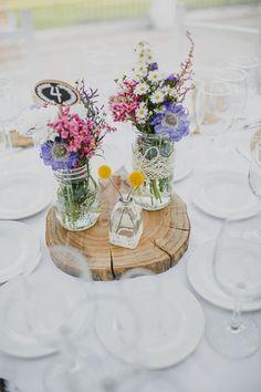 Flores silvestres en botes de cristal decorados con puntillas. En el botecito pequeño, un par de craspedias.