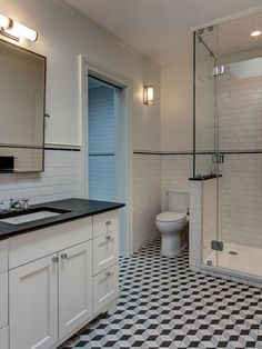 From the cubic pattern on the floor to the sharp line of the chair rail, this Brooklyn bathroom is a study in crisp geometry. The clean black-and-white color palette is uninterrupted, and traditional elements like the footed, furniture-style vanity and subway tile walls keep the area grounded.