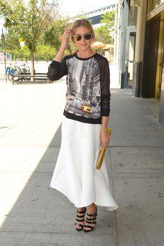 Olivia Palermo con una sudadera estampada de  Elie Tahari for DesigNation, falda blanca asimétrica y sandalias negras de tiras de charol de Christian Louboutin.