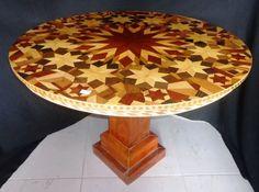 Mesa executada em madeira com tampo em rico trabalho de marcheterie no formato redondo, coluna central quadrada.