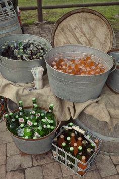 Galvanized buckets of drinks on make shift barrel tables.