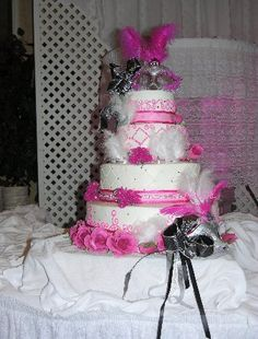 This Quinceanera cake has a masked ball theme. It's covered with Masks, feathers, diamonds and pink roses.