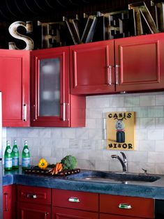 Large metal letters add an unexpected, whimsical touch to this vibrant kitchen, which also features red cabinetry and fun art above the sink.