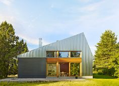 Metal-clad House L's low profile and simple pitched roof allows it to blend in effortlessly with the rural landscape.