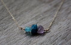 A trio of vibrant gemstones hang from a 14k gold filled or sterling silver chain.  From left to right- neon apatite, dark apatite, and amethyst.