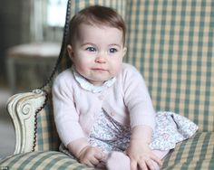 Princess Charlotte is wearing a floral print dress with a white frilled collar, the design...