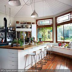 Dese helle Küchentheke mit Holzplatte wird durch die weißen Barhocker mit kurzer Lehne stilvoll ergänzt und schafft dadurch ein ästhetisches Bild. Das dunkelfarbige …