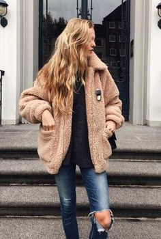 Peach shearling jacket over black top and distressed denim jeans.