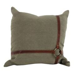 Canvas pillow with a leather strap design.   Product: PillowConstruction Material: Canvas, leather and fiber fillColor: Natural and brownFeatures: Insert includedDimensions: 17.7 x 17.7