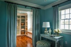 Conveniently located off of the master closet, a blue antique-inspired dressing table and tufted ottoman provide extra storage and an optimal spot to prepare for the day's events.
