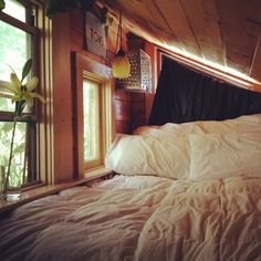attic bedroom nook // vaulted wooden ceiling // fluffy white bed // plants in the window