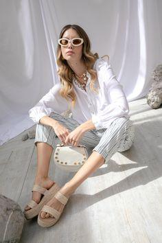 Camisa blanca Map, pantalon rayado con jareta Petite Studio, sandalias beige tejidas Steve Madden, clutch blanca Coccinelle, lentes blancos ovalados Metor Amour y cadena con perlas Map.